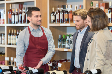 wine seller recommending bottle to young couple