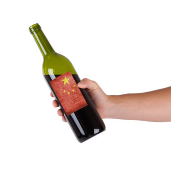 Hand holding a bottle of red wine, label of China, isolated on white,