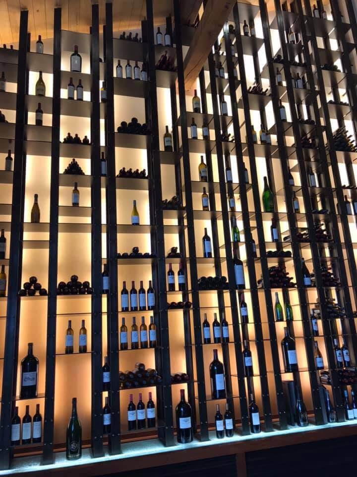 Etagère éclairée avec de nombreuses cases aux formes irrégulières pour présenter des bouteilles de vins