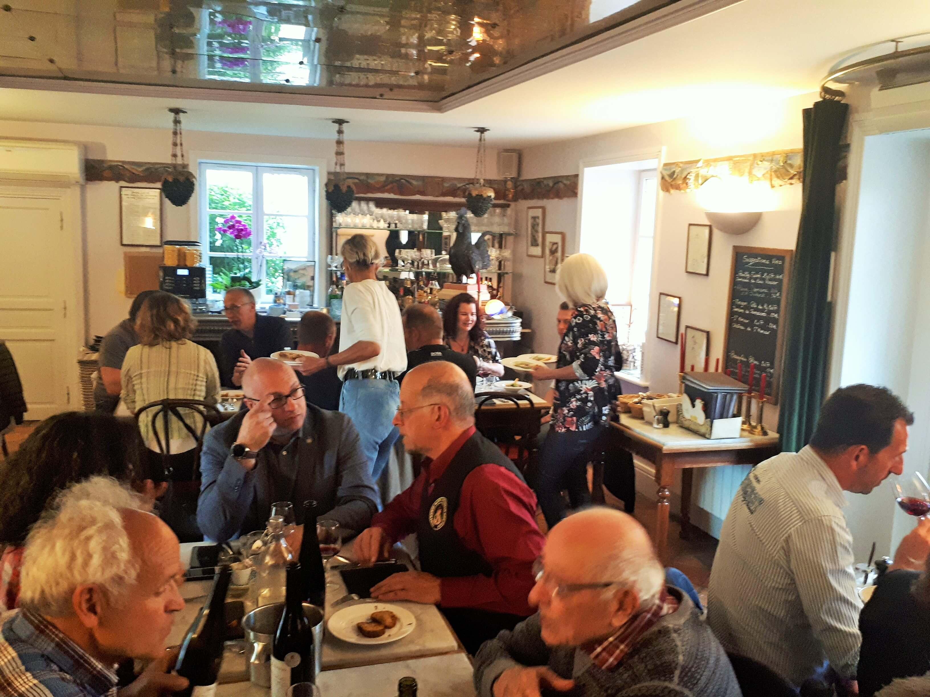 Ambiance chaleureuse entre cavistes et vignerons au restaurant Coq à Juliénas
