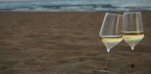 deux verres de vin blancs sur une plage au soleil couchant